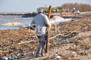 stock-photo-24710181-man-on-the-dirty-beach-takes-away-pieces-of-wood